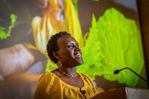 Dr Ngumbi speaking in a yellow shirt with plant presentation behind her