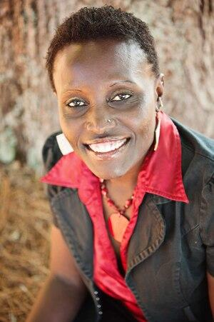 Dr. Ngumbi smiling in a red button up shirt with a black blazer jacket over it.